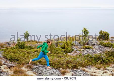 La Svezia, Uppland, Runmaro, Barrskar, ragazzo (6-7) in esecuzione dal mare Foto Stock
