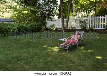 Senior L Uomo A Prendere Il Sole In Giardino Ascoltando Gli