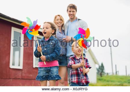 I genitori a guardare i bambini giocare con pinwheels Foto Stock