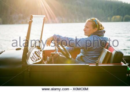 Vista laterale giovane donna seduta nel carrello rinnovato e guardare il tramonto, Idaho, Stati Uniti d'America