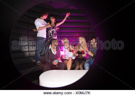 Coppia giovane ballare in un night club con i loro amici mentre sorseggiate un drink Foto Stock