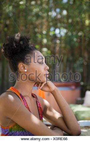 Profilo di pensieroso donna seduta sul patio Foto Stock