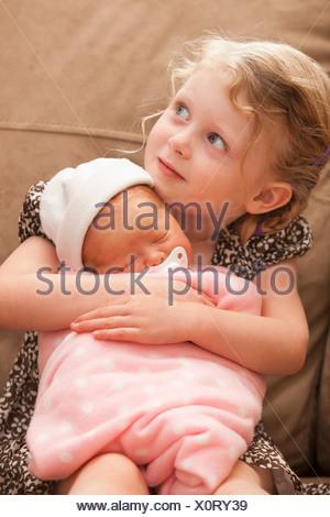 Stati Uniti d'America, Utah, Lehi, ragazza (2-3) abbracciando la sorella del bambino sul divano Foto Stock