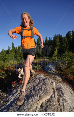 Donna e cane trail running sulla montagna Hollyburn, Cypress Bowl, West Vancouver. British Columbia. Canada Foto Stock