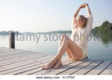 Giovane donna rilassanti sul Lago di pier Foto Stock