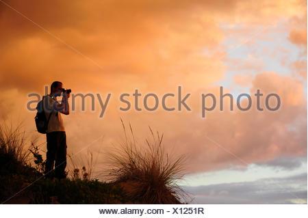 Silhouette di un fotografo di natura nelle dune del bagliore di sera, Grecia, Peloponneso, Messenia Foto Stock