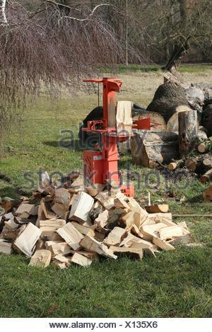Pila di cubi di legno e attrezzo di taglio sui pascoli Foto Stock