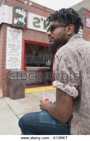 Un giovane uomo seduto e mangiare yogurt surgelato. Foto Stock
