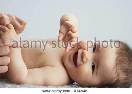 Un bambino sdraiato tenendo la sua madre le mani Foto Stock