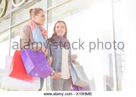 Giovani donne il trasporto delle borse della spesa da negozio a negozio Foto Stock