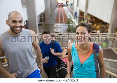 Ritratto sorridente amici su scale presso la palestra Foto Stock