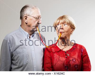 Coppia senior pasticceria condivisione contro uno sfondo bianco Foto Stock