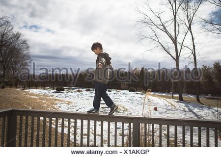 Ragazzo camminando lungo la parte superiore della recinzione in posizione di parcheggio Foto Stock