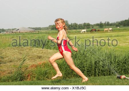 Bambino in esecuzione al di fuori a giocare con l'acqua dal tubo flessibile da giardino Foto Stock