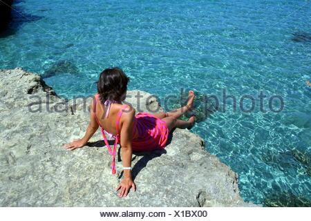 Donna seduta sulle rocce dal mare, Otranto e Lecce e Salento Puglia, Italia Foto Stock
