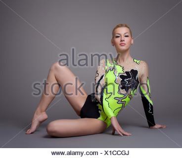 Giovane donna in tuta ginnasta in posa su grigio Foto Stock