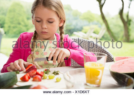 Ragazza al tavolo del patio per affettare le fragole fresche Foto Stock