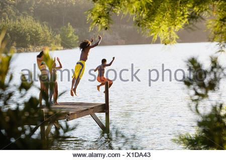 Padre e figlio 8 10 in costume da bagno salta fuori jetty nel lago di madre e figlia 7 9 il tifo vista posteriore Foto Stock