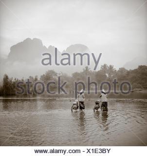 Due donne che indossano conica cappelli asiatici spingere le biciclette attraverso un fiume poco profondo in Vang Vien, Laos. Foto Stock