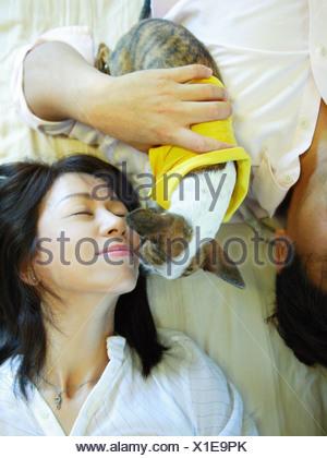 Angolo di alta vista di una metà adulto giovane sdraiato sul letto con un chihuahua cucciolo Foto Stock