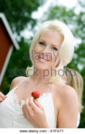 Una donna che mantiene una fragola, Svezia. Foto Stock