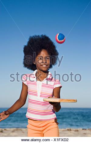 Ragazza 8 10 giocando con il bat e la sfera sulla spiaggia sabbiosa sorridente vista anteriore verticale Foto Stock
