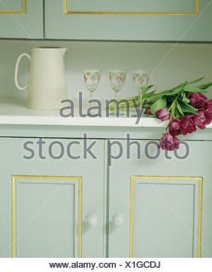 Close-up di tulipani rossi accanto a Caraffa del Bianco e vino-bicchieri sul piano di lavoro di colore bianco al di sopra di turchese pallido armadio Foto Stock