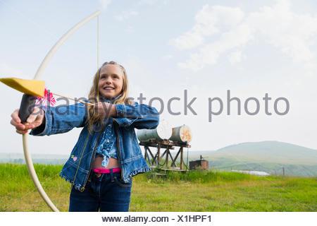 Ragazza che gioca con arco e frecce nel campo Foto Stock