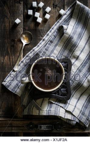 Acqua calda tazza di tè in legno rustico trivet e lino al buio su un vassoio di legno con cubetti di zucchero e cucchiaio vintage. Foto Stock