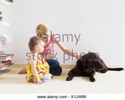 Madre con bambino figlia (12-17 mesi) giocando con il cane Foto Stock