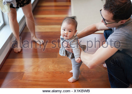 Padre aiutando bambina di stand Foto Stock