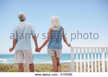 Coppia senior tenendo le mani sul patio beach Foto Stock