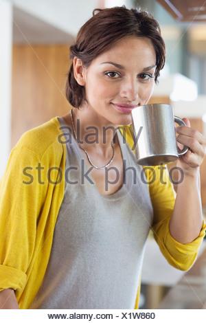 Donna di bere il tè alle erbe in cucina Foto Stock