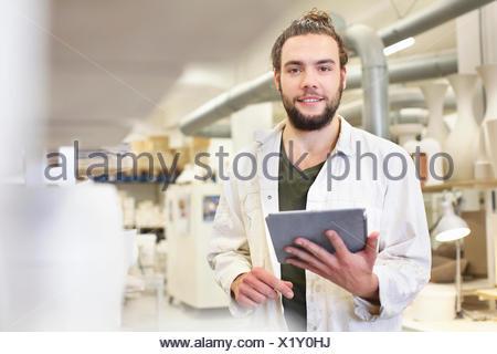 Potter maschio utilizzando tavoletta digitale nel laboratorio di ceramica