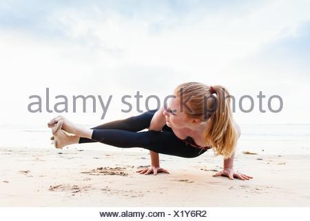 Metà donna adulta in bilico in posizione di yoga sulla spiaggia Foto Stock