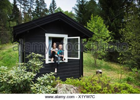 Ragazze seduta nella finestra di shack Foto Stock