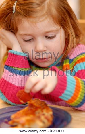 Ragazza 4 anni di mangiare la pizza a giocare con il cibo Foto Stock