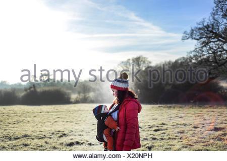 Donna in ambiente rurale, portando i giovani nella baby sling Foto Stock
