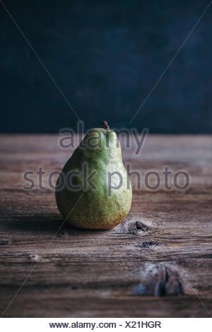 Singola pera su una tavola in legno rustico Foto Stock
