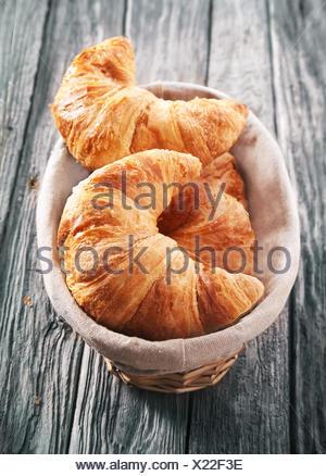 Angolo di alta vista di pane appena sfornato a scaglie golden croissant in un cestello servita su un vecchio rustico tavolo in legno con una texture spiovente Foto Stock