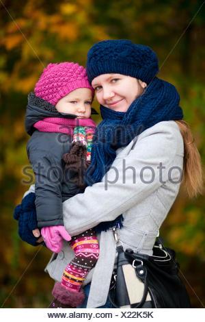 Madre cullano la figlia sia in abiti caldi con cappello di lana e sciarpa Foto Stock