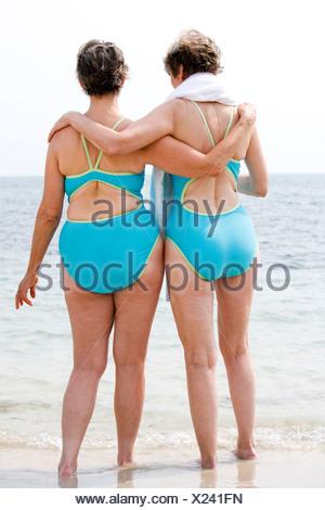 Ritratto di due donne senior a braccetto in spiaggia Foto Stock