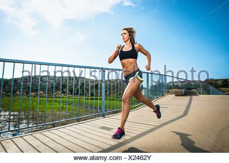 Athletic donna in esecuzione sul ponte Foto Stock