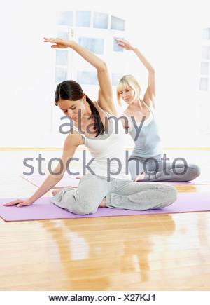 Germania, Amburgo, istruttore yoga e donna fare yoga esercizio in palestra Foto Stock