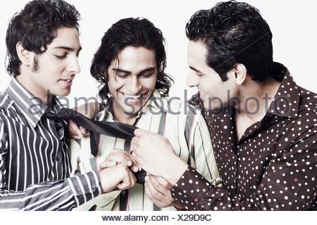 Close-up di due giovani uomini guardando un giovane di tirante Foto Stock