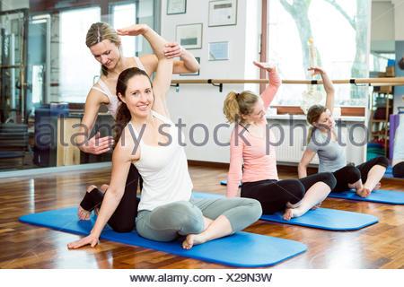 Istruttore sostiene le donne bracci di estensione nella classe di Pilates Foto Stock