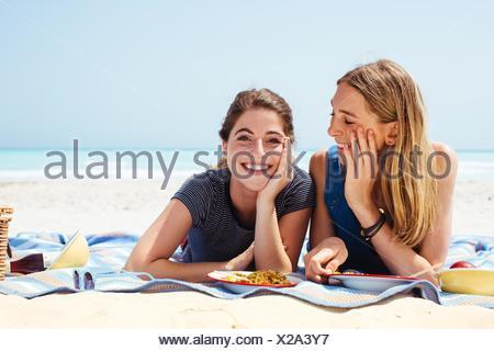 Ritratto di due giovani amici di sesso femminile che giace sulla coperta picnic in spiaggia Foto Stock