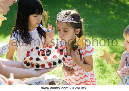 Ragazza soffiando le candeline sulla torta di compleanno a outdoor festa di compleanno Foto Stock