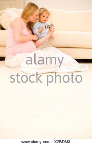 Donna incinta che mostra la fotocamera al bimbo figlio 15-18 mesi di divano Foto Stock
