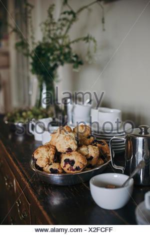 Pane appena sfornato muffin ai mirtilli in una ciotola su una rustica cabinet in legno Foto Stock